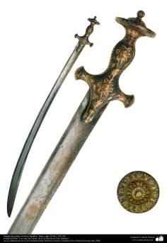 وسایل کهن جنگی و تزئینی - نمایی از شمشیر جنگی که دسته ان با نقوش گل تزئین شده است - هند ، قرن نوزدهم و هفدهم میلادی.