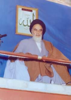 Imam Khomeini discursando e atrás dele um quadro com apalavra Allah (Deus)