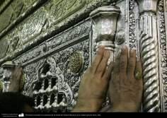 Peregrinos tocando los contornos de la tumba de Fátima Masuma en la ciudad santa de Qom, Irán.