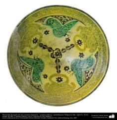 Plato hondo decorado con aves y motivos simétricos, – cerámica islámica – probablemente Nishapur de Irán - siglos X y XI dC.