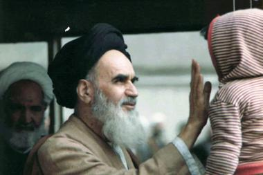Imam Khomeini brincando com uma criança