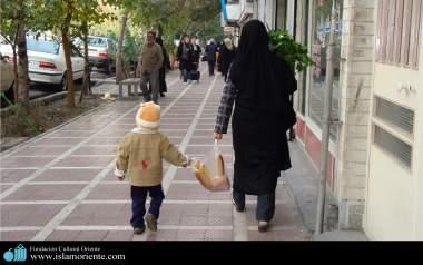 Mulher muçulmana e seu pequeno filho caminhando juntos