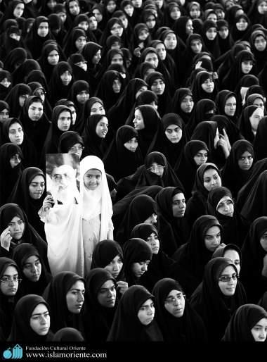 Menina muçulmana segurando a foto do Aiatolá Khomenei em um encontro religioso